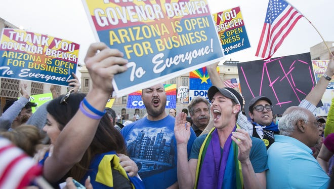 SB1062-- 226/14- Protestors, including Christopher Bullock, center, celebrate after hearing that Arizona Gov. Jan Brewer was going to veto the controversial SB 1062. Pat Shannahan/The Arizona Republic
