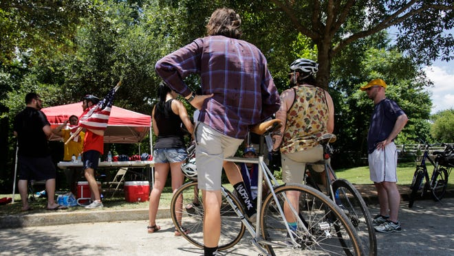 Cyclists gather at Rotary Point to sign a petition to keep the bike lanes on West Bayou Parkway intact in Lafayette July 2, 2016.
