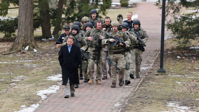 Police officers head to Salter Hall to release students and staff who had been told to shelter in place Wednesday, Feb. 17, 2016, on the campus of Wabash College in Crawfordsville. The campus had been on lockdown following a double homicide near Zionsville.