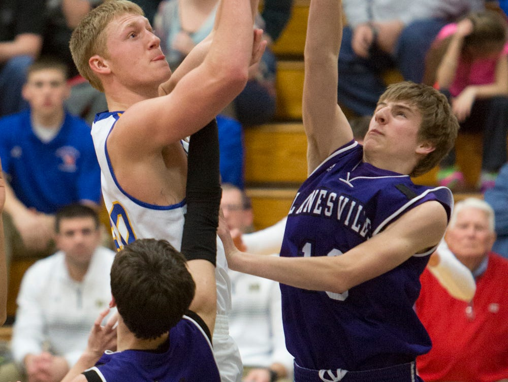 Lanesville's Luke Beach (11) and Riley Cook (15) attempt to block Zach Moore's shot during the second half of play, Friday, February 12, 2016, at New Washington High School in New Washington, In.