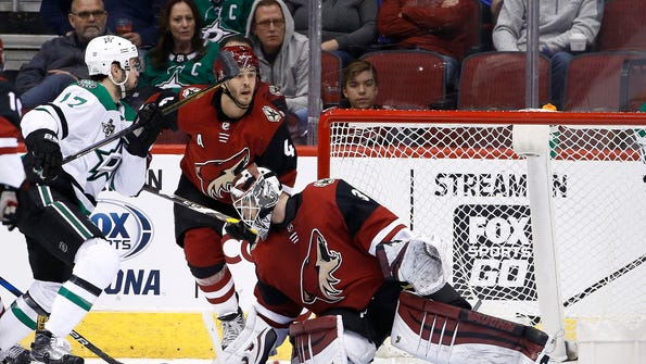 Dallas Stars center Devin Shore (17) flips the puck up and over Arizona Coyotes goaltender Scott Wedgewood, right, for a goal as Coyotes defenseman Niklas Hjalmarsson (4) watches during the second period of an NHL hockey game Thursday, Feb. 1, 2018, in Glendale, Ariz. (AP Photo/Ross D. Franklin)