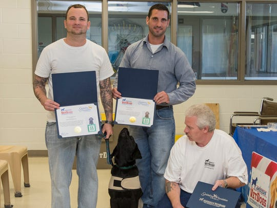Eastern Correctional Institution inmate and dog trainers Owen Rittenhouse, Jesse Barnes, and Lawrence Nichols pose with puppy Sunrise at the dog's graduation for the America's Vet Dogs program. Inmates completed a year-long training with the future service dogs then said farewell to their first pair of canine graduates. The dogs will receive final training at the America's Vet Dogs headquarters in New York before being placed with a wounded American veteran.