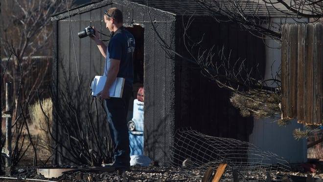 A Poudre Fire Authority investigator looks over a scene after a fire burned fences, four sheds and partially damaged a home on Larimer County Road 38E west of Taft Hill Road on Feb. 16.