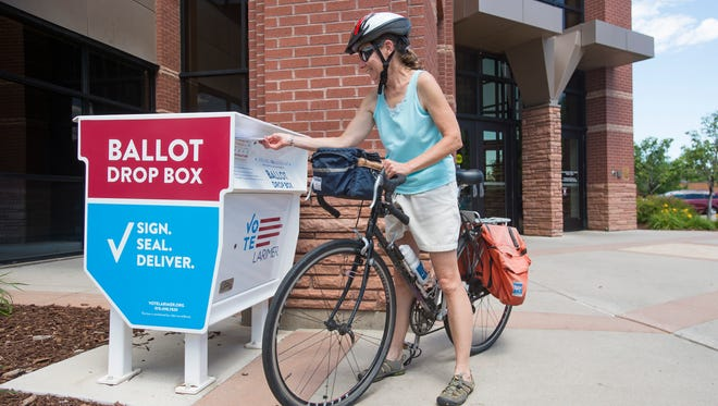 Beth Scott pauses from her bike ride to drop off her ballot at the Larimer County Courthouse on Monday, June 25, 2018.