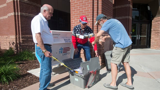 Jeff Bailey tosses his ballot in a collection box while Lary Steinhauer and Dave Jehu transport them for counting on Election Day, Tuesday, June 26, 2018.
