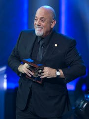 Billy Joel holds the Library of Congress Gershwin Prize for Popular Song at the end of a concert in his honor in Washington on Nov. 19, 2014.
