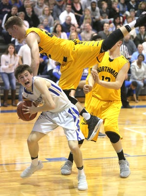 St. Peter's Caleb Stewart is fouled by Northmor's Brock Pletcher on Saturday.