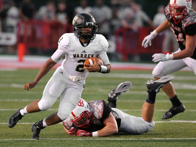 Warren Central quarterback Jordan Leach breaks away from a tackle from Center Grove's Cameron Tidd in the second half of the season opener held at Center Grove High School on Friday, August 22, 2014. Warren Central won 12-9 in overtime.
