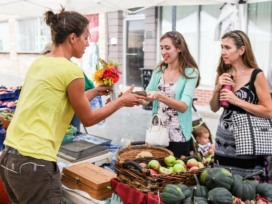 Helen Chandler of Whistling Wolf Farm in Pittstown, left, sells flowers to Larissa Clause, left, and her mother, Christine Clause, both of Whitehouse Station, at the Somerville Farmers Market on the Division St. pedestrian mall on August 20, 2015.