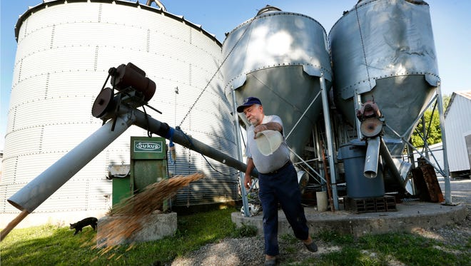 Chris Petersen throws feed to a skid loader on his farm, in Clear Lake, IA. Farm groups and some members of Congress from farm states are decrying proposed cuts to crop insurance and other safety net programs for farmers included in President Donald Trump's budget.