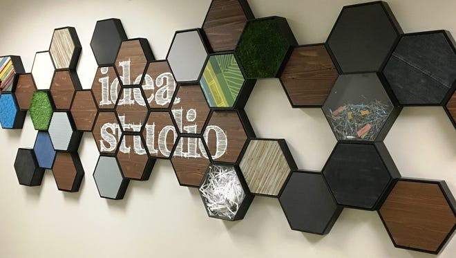 The Idea Studio sign is made from a variety of mediums, including reclaimed wood, old book spines, shredded paper, chalk board and more.