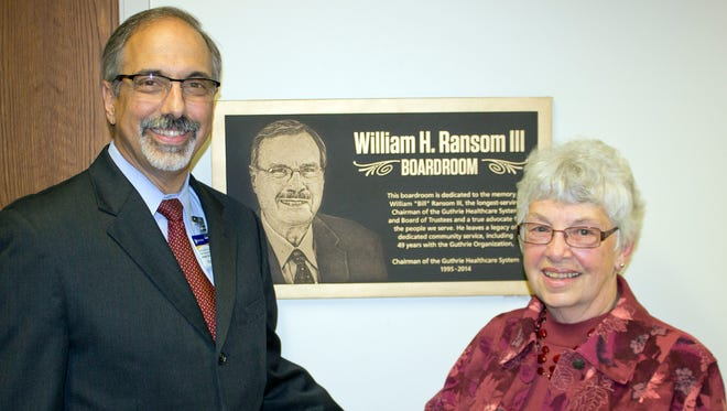 Dr. Joseph Scopelliti and Sarah Ransom stand in front of the dedication plaque at the boardroom on the Guthrie Sayre campus.