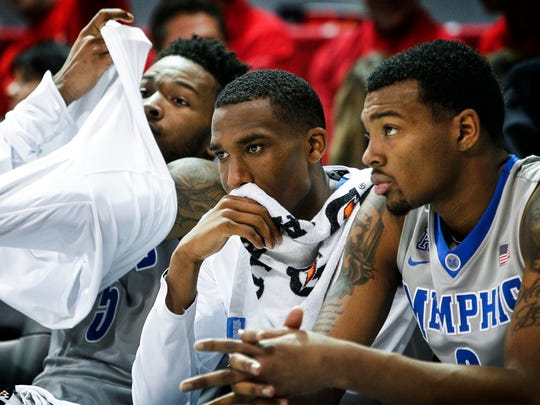 University of Memphis teammates (left to right) Markel Crawford, Jeremiah Martin, and K.J Lawson watch from the bench as the Tigers fall to Southern Methodist University 103-62 at Moody Coliseum in Dallas, Texas.