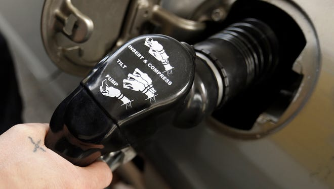 Instructions are visible on a handle as gas is pumped at a station in Portland, Ore., Wednesday, May 6, 2015.Oregon is one of just two states where motorists aren't allowed to pump their own gas. The other is New Jersey.  Now the Oregon Legislature appears ready to at least let people driving through rural Oregon pump their own. (AP Photo/Don Ryan)