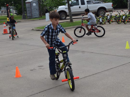 """Sladen Baker, 7, of Pineville rides his new bike around an obstacle course Thursday at Laborde Earles Law Firm in Marksville. The Laborde Earles Law Firm gave away 231 children's bikes and helmets to children in the Lafayette and Central Louisiana areas as part of their """"Bike It Forward"""" program, which promotes community involvement, child safety, child health and well-being."""