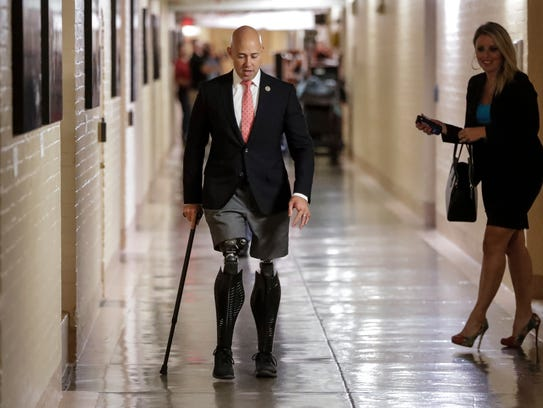 Rep. Brian Mast, R-Fla., walks to a meeting with fellow