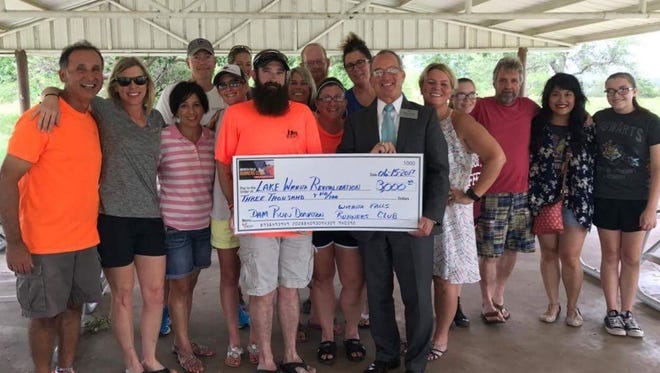 The Lake Wichita Revitalization Committee Chairman Steve Garner, front right, accepts a check for $3,000 from the Wichita Falls Runners Club.