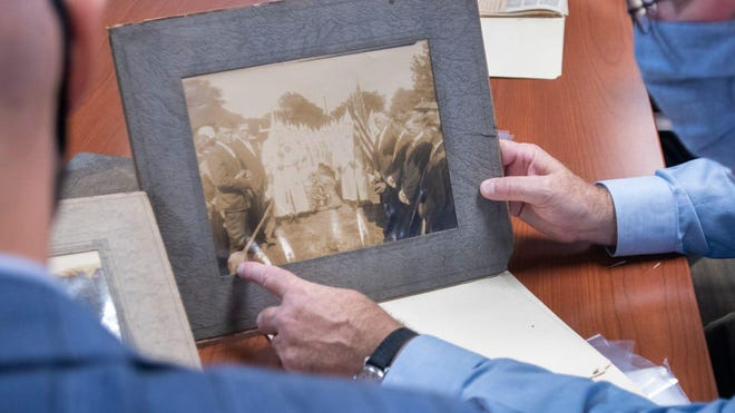 Jamin Wells, assistant professor and director of the public history master's program, left, and Rob Overton, executive director, look at a photograph as a UWF Historic Trust team catalogs Ku Klux Klan artifacts from T.T. Wentworth, Jr. at the Voices of Pensacola Multicultural Center in downtown Pensacola on Monday, July 20, 2020.