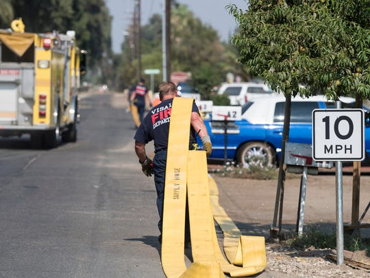 Visalia Fire Department picks up hose line after a