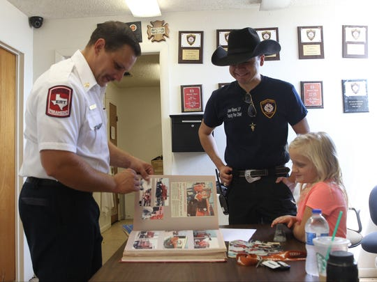 Grape Creek Volunteer Fire Department Chief Aaron Flint flipped through a scrapbook looking at old photos and clip-out articles on the department next to Deputy Fire Chief Jose Rivera. Flint's daughter looked along with her father.