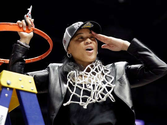 South Carolina head coach Dawn Staley salutes the fans after she cut down the net following her team's win over Mississippi State in an NCAA college basketball championship game at the women's Southeastern Conference tournament Sunday, March 4, 2018, in Nashville, Tenn. (AP Photo/Mark Humphrey)