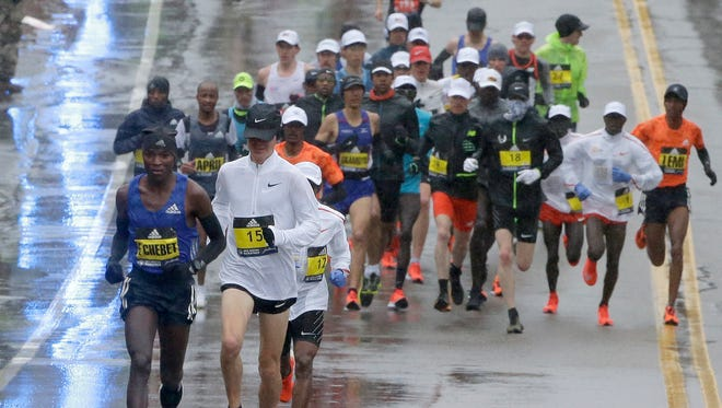 Evans Chebet, left, of Kenya, and Arne Gabius (15), of Germany, lead the men's elite field of runners during the second mile of the 122nd Boston Marathon on Monday, April 16 in Hopkinton, Mass.