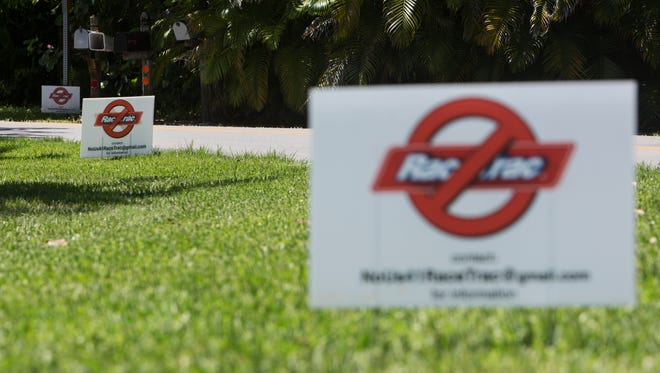 In this file photo, RaceTrac opposition signs line Frederick Street on June 29, 2016 in Naples.
