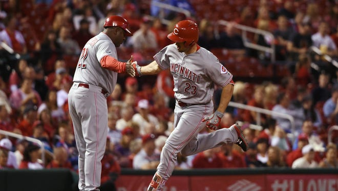 Reds left fielder Adam Duvall celebrates with third base coach Billy Hatcher after hitting a solo home run off of Cardinals starting pitcher Jaime Garcia during the first inning.