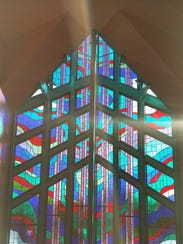 The stained-glass windows in the tower feature an abstract