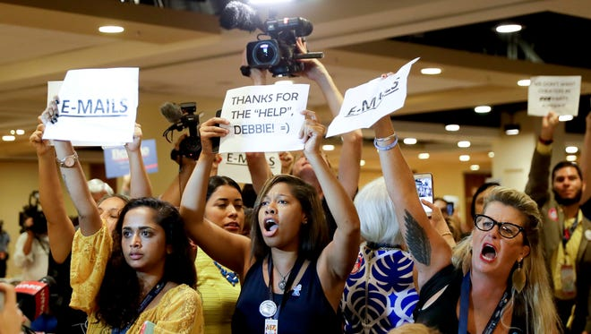 Protesters yell as DNC Chairwoman Debbie Wasserman Schultz arrives for a Florida delegation breakfast in Philadelphia during the first day of the Democratic National Convention.