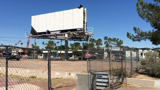 An imposing billboard adorns the prominent corner at two of Phoenix's biggest thoroughfares: Central Avenue and Camelback Road. The otherwise-empty corner is fenced off.