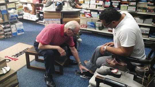 Ed Davis (left) measures a customer for shoes at his Medford store in this 2014 photo. Davis will retire at the end of this year after 45 years in business.