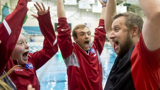 St. Clair coach Ken Sygit and his swimmers react as he is named the swim coach of the year at the state swim meet at Eastern Michigan University in Ypsilanti, Mich. on Saturday, Nov. 21, 2015.