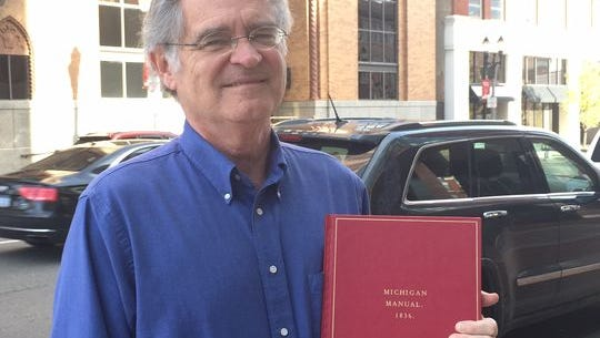 Chris Carl, a former editor of the Michigan Manual, holds a replica of the first edition, from 1836.