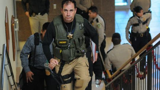 Doña Ana County Sheriff's detective Ken Roberts heads up the stairs of the County Government Center with deputies on Tuesday, Dec. 8, 2015, to execute a search warrant within the county administration offices on the second floor.