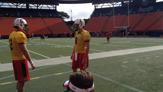 Hayden Moore (right), shown at a UC practice this week at Aloha Stadium, will start the Hawaii Bowl in place of Gunner Kiel.