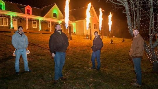 Wall Christmas Light Show organizers posing for a photo as the pyrotechnics erupt at a trial run. From left: Mike Roberti, Brian Brateris, Trevor Ferguson and Dan Brateris.