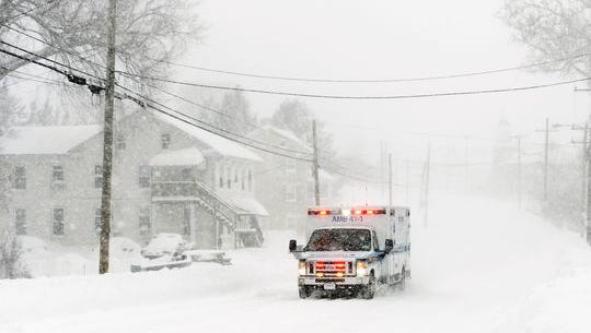 An ambulance drives down a snow-covered street.