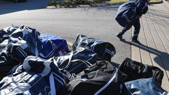 Hockey players pick up their gear outside A-Game Sportsplex on Thursday.