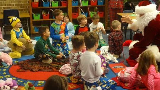 Children at Pea Ridge Elementary School listen to Santa, who was brought in via fire truck by Whiting Field's Helicopter Training Squadron 18