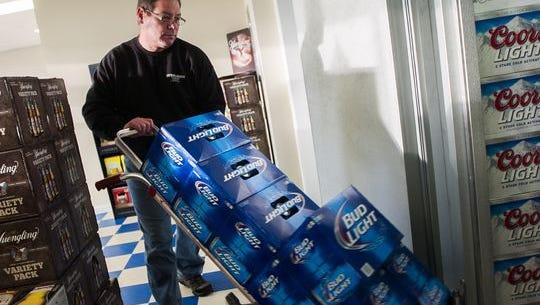 Case Beer & Beverage owner Dan Gladhill stocks cases of beer in the freezer at the beer distributor in Hanover in 2013.