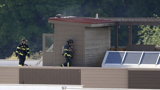 Firefighters work on the roof of a complex on the 200 block of South Riverheath Tuesday, May 24, 2016 in Appleton