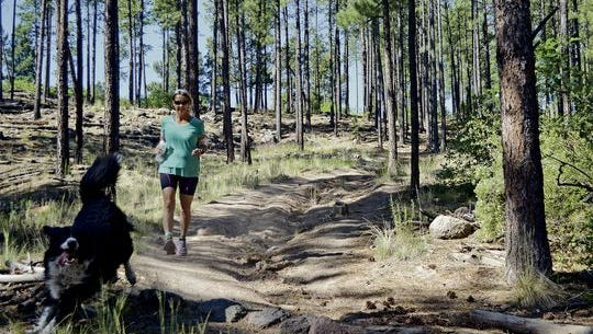 Karen Williams and her dog Princess run a trail near Barranca Mesa at Los Alamos on Monday June 27, 2016. Williams was mauled by a mother bear during a marathon at the Valles Caldera National Preserve recently. The bear was euthanized, required under state law for rabies testing. Willaims thinks the law needs to change.