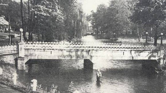 An old photograph shows the bridge from the village
