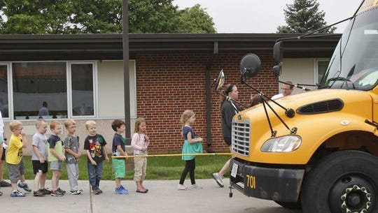 """Children board a bus while learning about bus safety during Ankeny Safety Town 2013 held at Northwest Elementary School June 5. Safety Town is a week-long program for children entering kindergarten in the fall. Each session includes safety instruction for biking, traffic, fire, stranger danger, boating, camping, bus, poison, gun, internet, weather, pedestrian, pool, electric, seat belt, personal safety and 911 emergencies. A new topic this year is window safety with information from the Hannah Geneser Foundation. Children get to ride bikes in """"Safety Town,"""" travel to the fire department, go on a school bus ride, practice a tornado drill and meet Vince and Larry the crash dummies."""