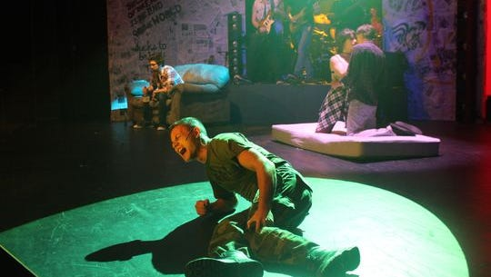 """Talk about being timely. Three friends from suburbia have different takes on the American Dream in a post-9/11 world when New Stage Theatreworks presents the post-punk band Green Day's musical version of """"American Idiot"""" at 8 p.m. Friday through Sunday at Theatre Tallahassee, 1861 Thomasville Road in Betton Hills. The album went to No. 1 in England this month for some strange reason. Shown here, Tunny (Santos Sanchez) gets shot during the War on Terror, while Whatsername (Jilian Wesolowski) and Johnny (Aron Wesolowski) embrace, as Will (Jacob Williams) stays stuck unhappy at home in """"Give Me Novocaine."""" Tickets are $18 and $20. The play contains profanity and adult themes. Visit nstw.tix.com."""