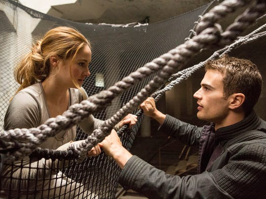 "This image released by Summit Entertainment shows Shailene Woodley, left, and Theo James in a scene from ""Divergent."" The movie releases on Friday, March 21, 2014."
