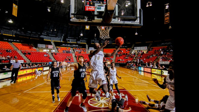 ULM's Prince Cooper (14) goes up and under McMurry's Aaron Gettys on Friday afternoon at Fant-Ewing Coliseum. The Warhawks beat the visiting War Hawks 88-43.