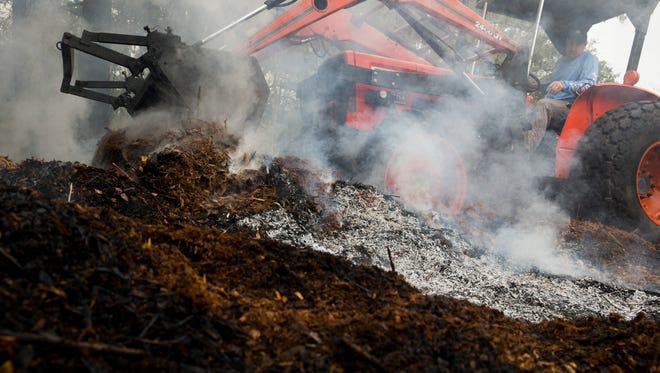 Jonathan Whitlow and his wife Shaina Muth, along with their one-year old son River, inspect their property as Jonathan covers up a burning pile of mulch Sunday, April 23, 2017 in Golden Gate Estates. Irrigation equipment, a water reservoir, tools, and a couple of sheds were lost in the 30th Avenue Brush that swept across eastern Collier County Friday. The couple had plans to turn it into a family farm.