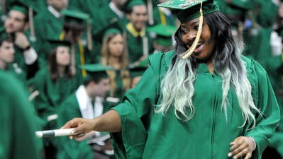 An MSU graduate jokes with friends after receiving her diploma at a December 2014 commencement. New college graduate have better odds of landing a job, an MSU study has found.